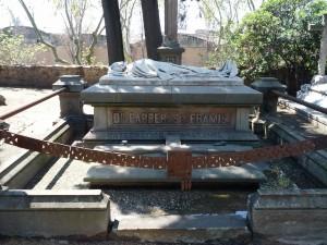 Man sieht ein steinernes Skelet auf einem Grabstein liegen