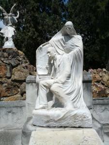 Morbide Skulptur des Verstorbenen mit Geißt im Hintergrund