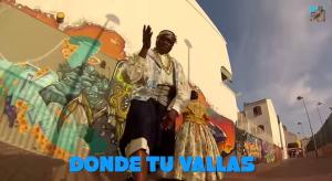 Das Bild zeigt den Rapper Lory Money in traditioneller Kleidung vor eine Graffittiwand in Valencia
