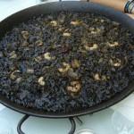 Eine Paella-Pfanne mir schwarzem Reis